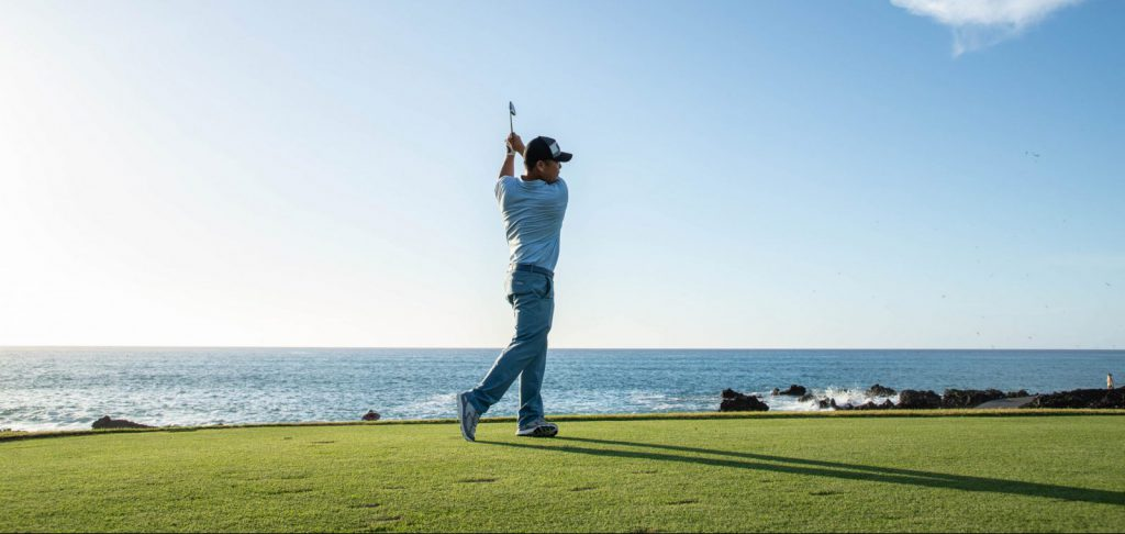 Garratt Okamura golf pro finishes swing with a blue sky and the ocean in the background