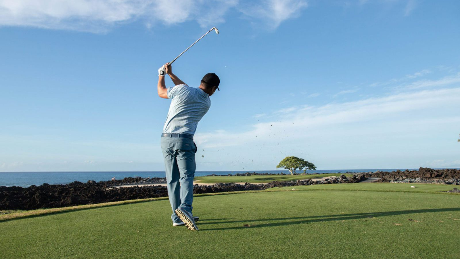 Garratt Okamura golf pro hits golf ball looking towards a blue sky and the ocean
