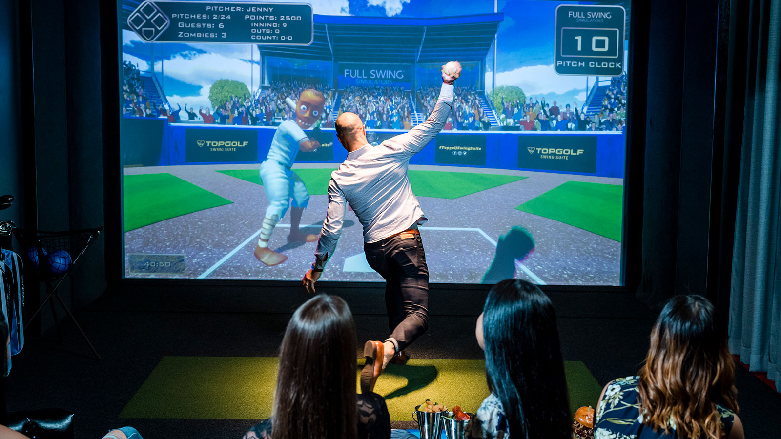 Group of adults watch man pitch a baseball in a virtual baseball game with TOPGOLF SWING SUITE