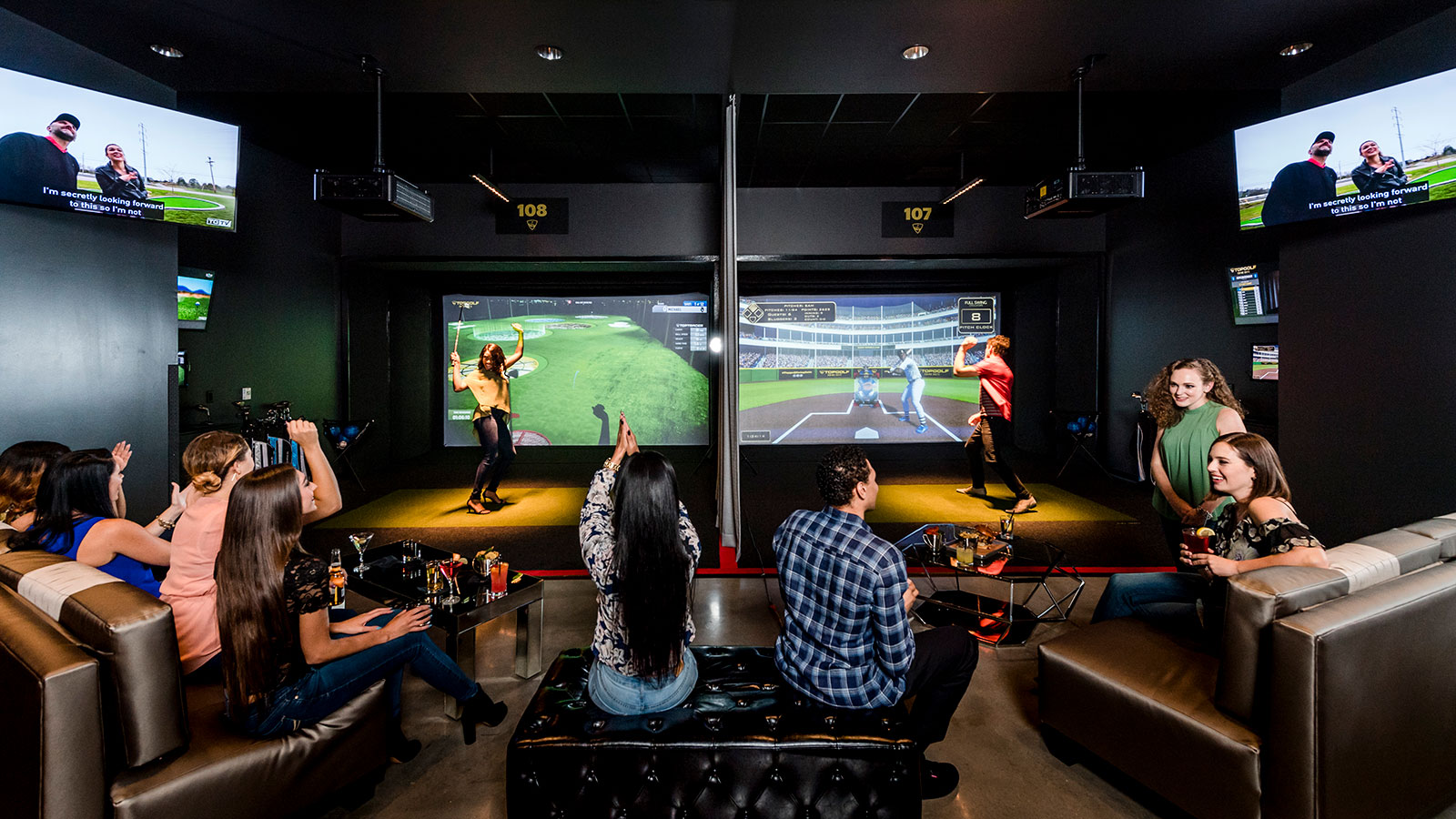 Group of adults socialize and watch others play virtual golf and baseball in the TOPGOLF SWING SUITE