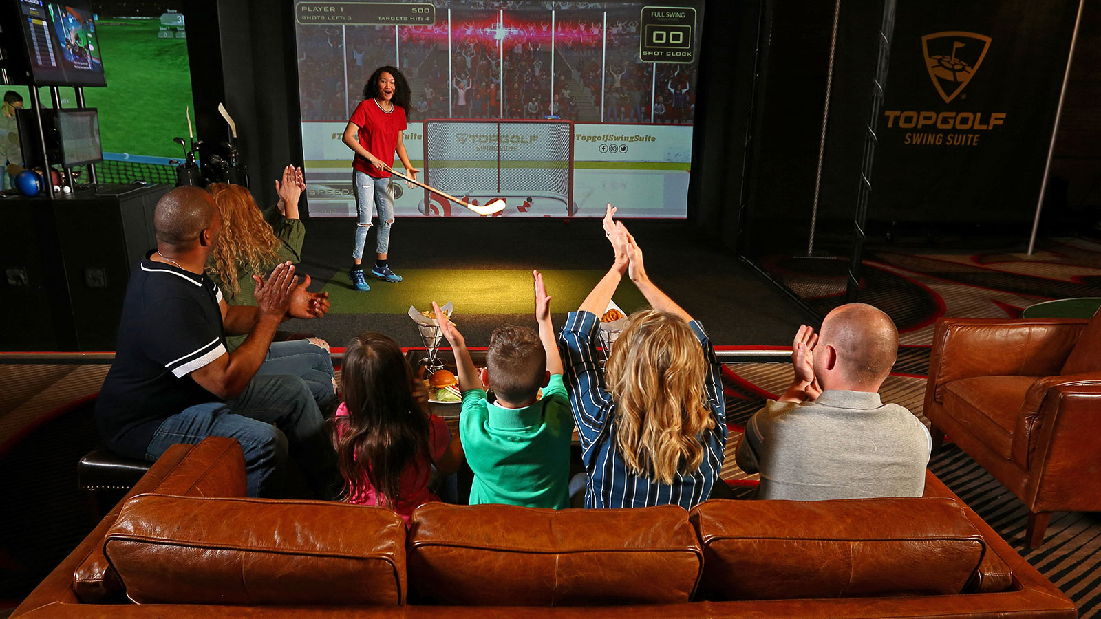 Group of adults and children cheer on woman playing virtual hockey with TOPGOLF SWING SUITE