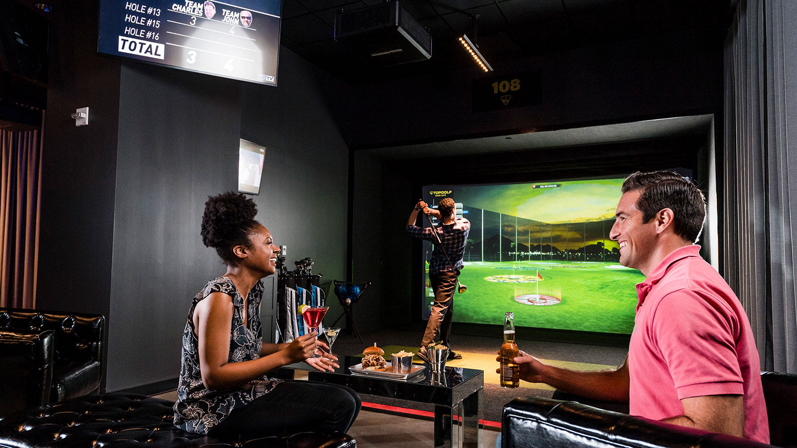 Man in pink colored golf shirt holds a beer across from woman in patterned tank top holds a cocktail and man behind swing golf club while playing TopGolf Swing Suite