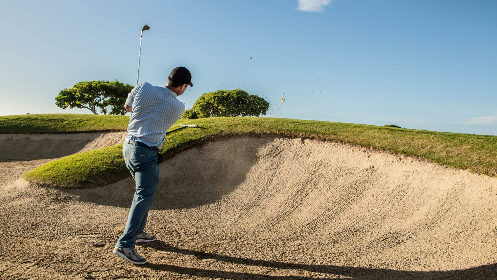 Golf pro Garratt Okamura hits ball out of sand trap on course
