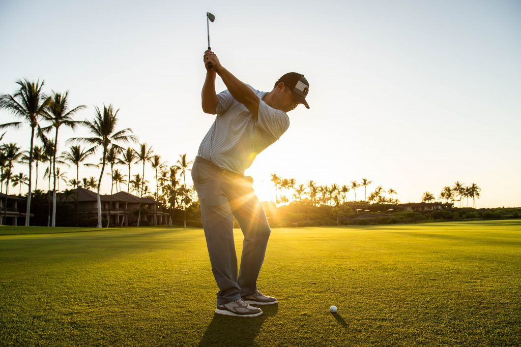Golf Pro Garratt Okamura takes a swing a golf ball with setting sun in background