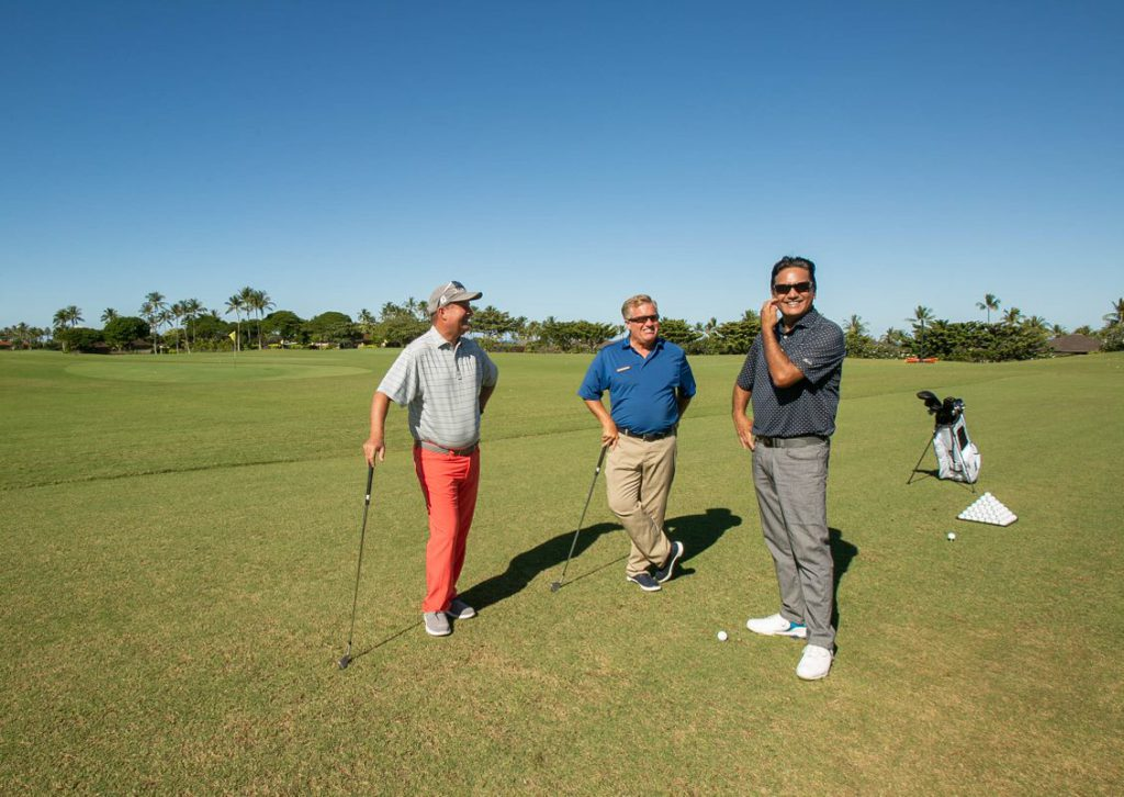 Three Golf pros standing on golf course smiling