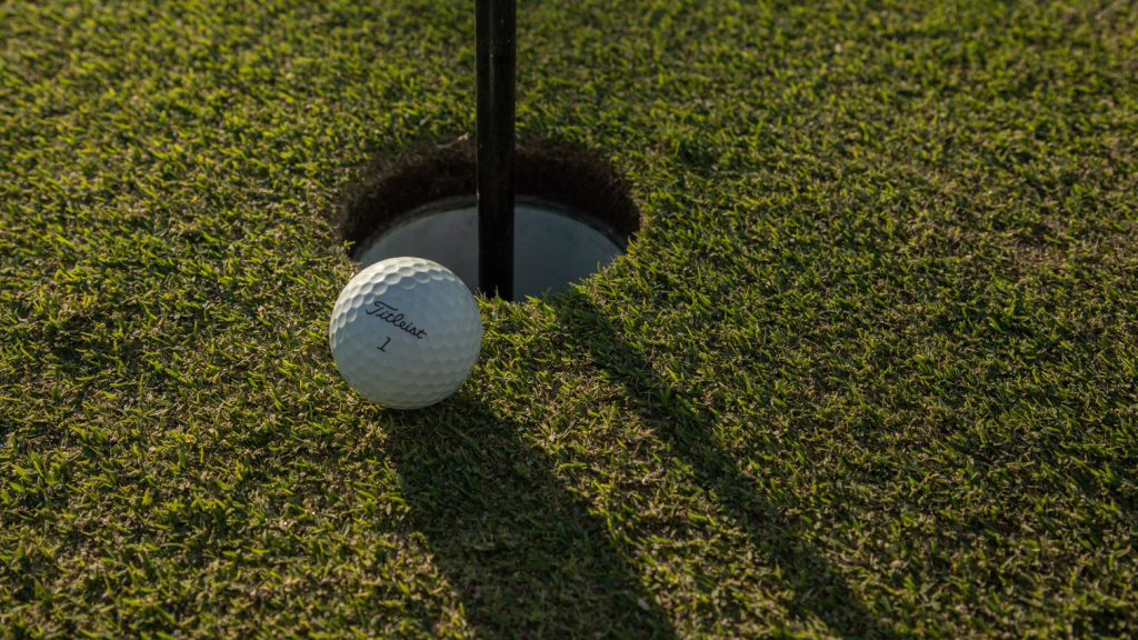 golf ball beside a golf hole with flag stick still in hole