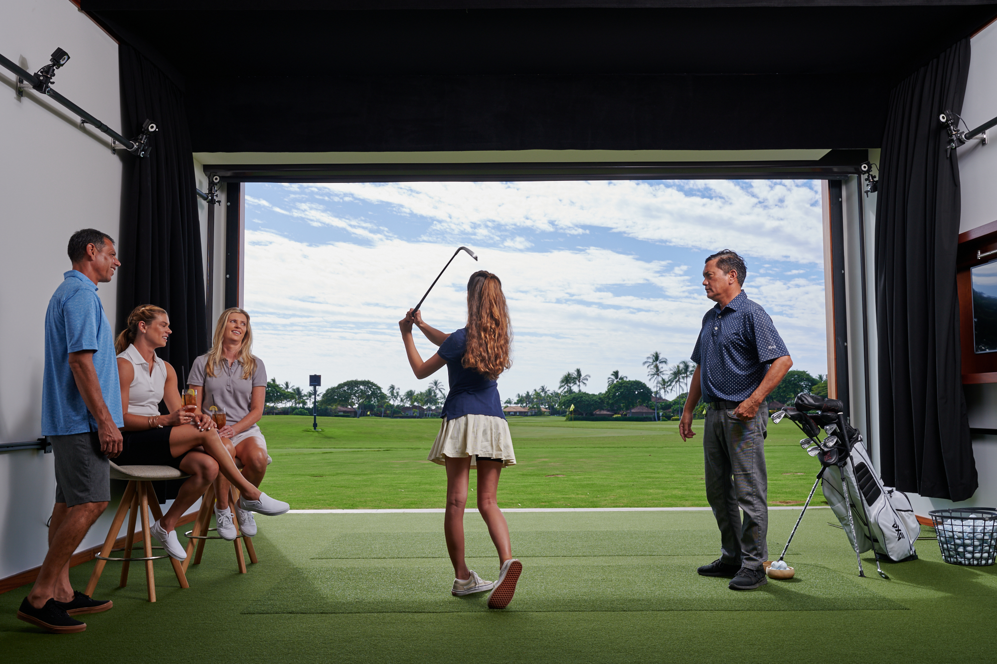 An instructor watches a girl swing while the family of three look on.