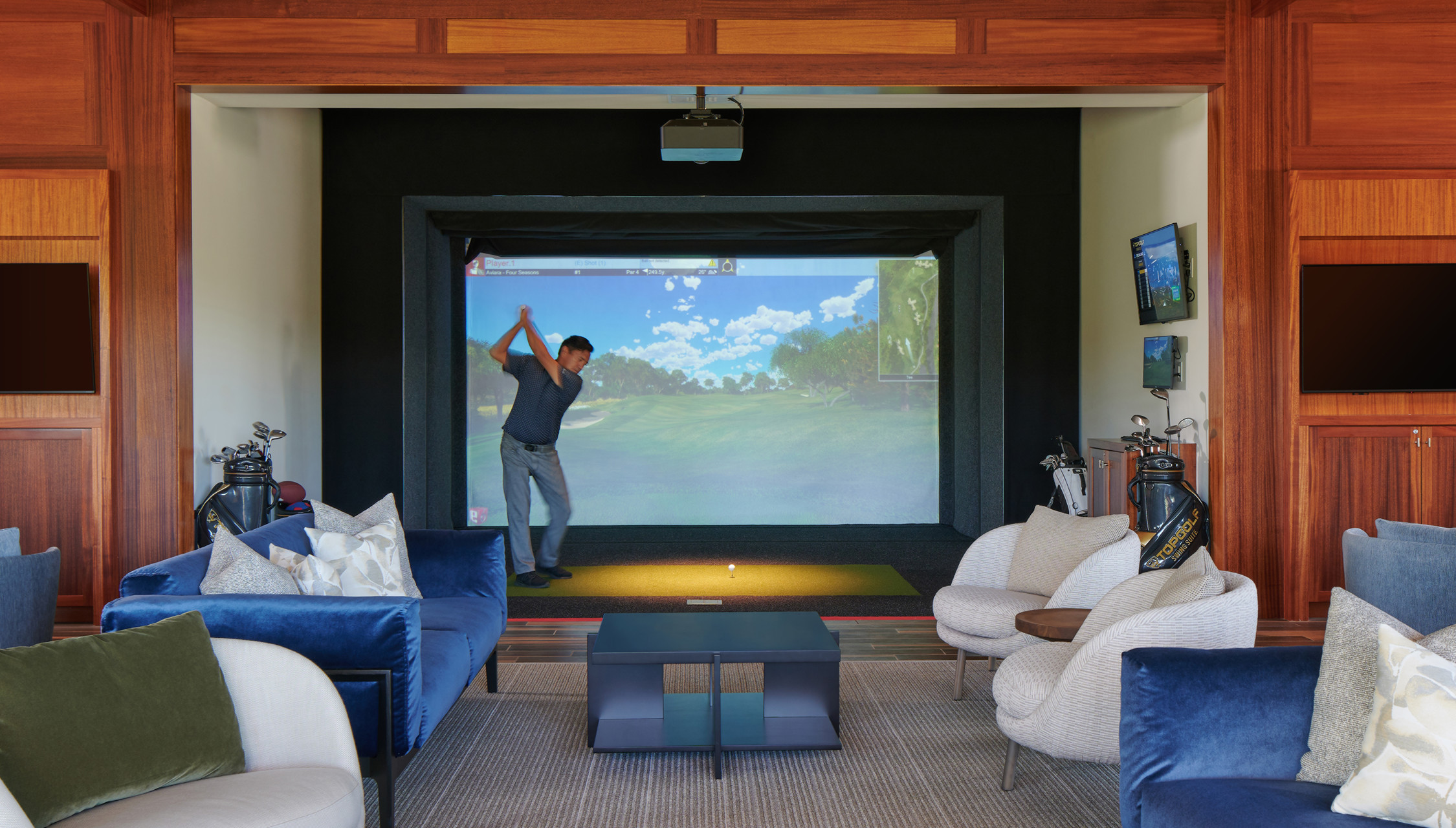 A room filled with comfortable seating has a screen with a golf course in the center, and a golf participant swinging.